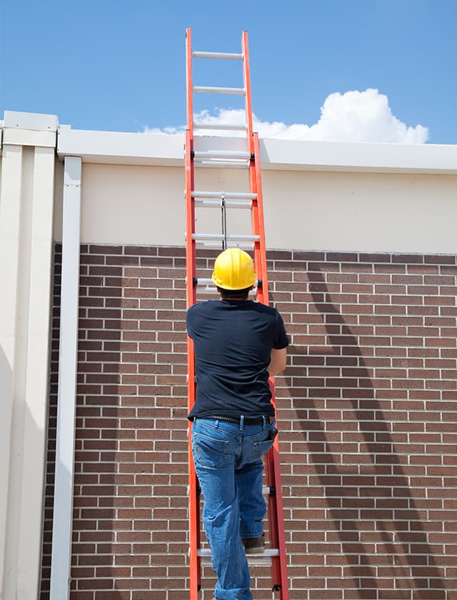 climibing a ladder on a Denver commercial roof repair project